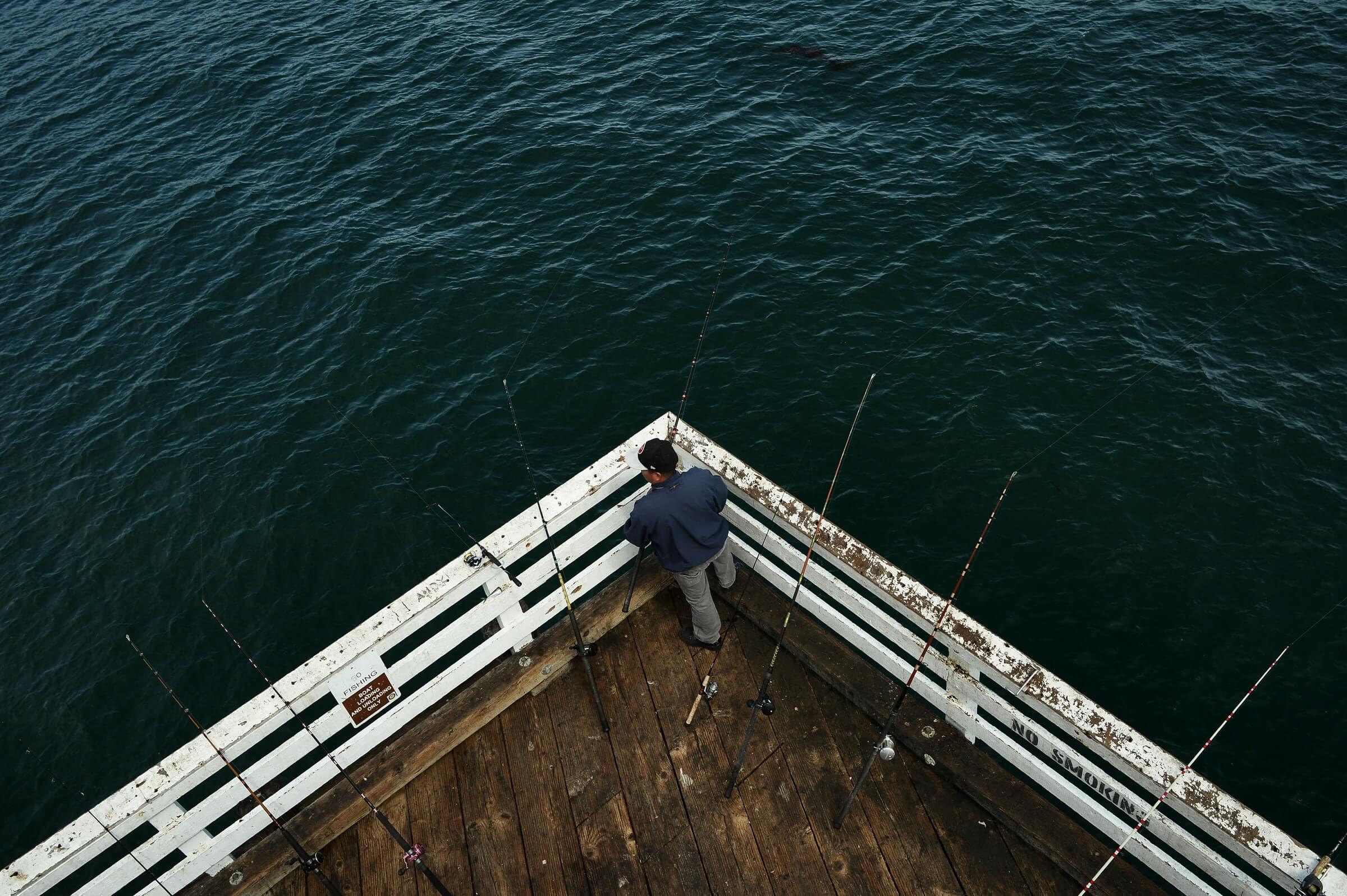 pêcheur avec ses cannes à pêche sur un pont